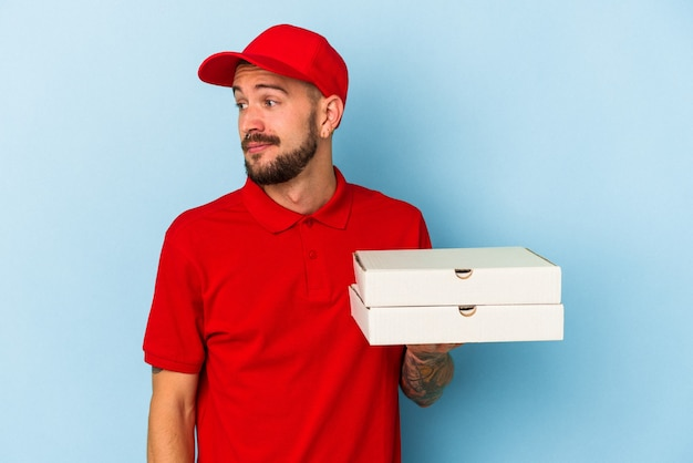 Young caucasian delivery man with tattoos holding pizzas isolated on blue background  looks aside smiling, cheerful and pleasant.