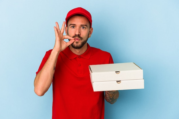 Young caucasian delivery man with tattoos holding pizzas isolated on blue background  with fingers on lips keeping a secret.