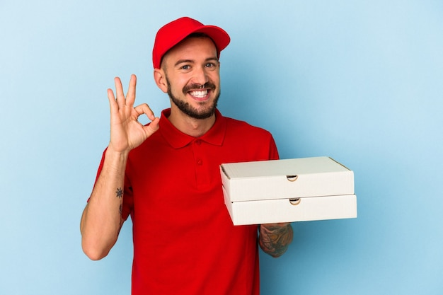 Молодой кавказский доставщик с татуировками, держащий пиццу, изолированную на синем фоне, веселый и уверенный, показывая одобренный жест.