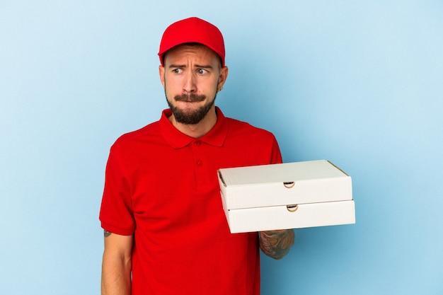 青い背景に分離されたピザを保持している入れ墨を持つ若い白人配達人は混乱し、疑わしく、不安を感じています。