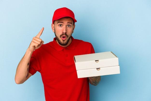 アイデア、インスピレーションの概念を持っている青い背景に分離されたピザを保持している入れ墨を持つ若い白人配達人。