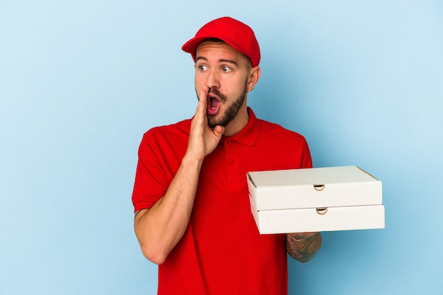 青い背景に分離されたピザを保持している入れ墨を持つ若い白人配達人は秘密の熱いブレーキングニュースを言って脇を見ています