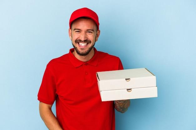笑って楽しんで青い背景に分離されたピザを保持している入れ墨を持つ若い白人配達人。