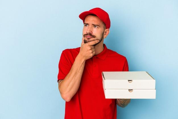 疑わしいと懐疑的な表現で横向きに見える青い背景に分離されたピザを保持している入れ墨を持つ若い白人配達人。