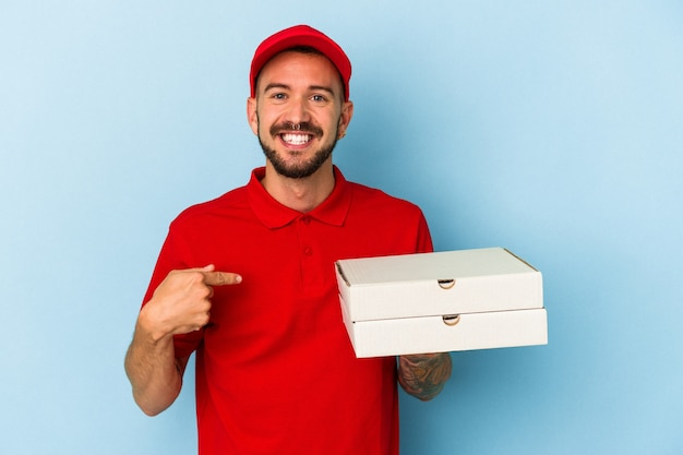 誇りと自信を持って、シャツのコピースペースを手で指している青い背景の人に分離されたピザを保持している入れ墨を持つ若い白人配達人