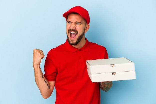 勝利、勝者の概念の後に拳を上げる青い背景に分離されたピザを保持している入れ墨を持つ若い白人配達人。