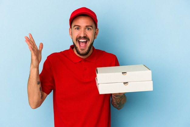 青い背景に分離されたピザを保持している入れ墨を持つ若い白人配達人は、嬉しい驚きを受け取り、興奮し、手を上げます。