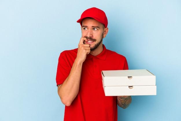 Молодой кавказский доставщик с татуировками, держащий пиццу, изолированную на синем фоне, расслабился, думая о чем-то, глядя на пространство для копирования.