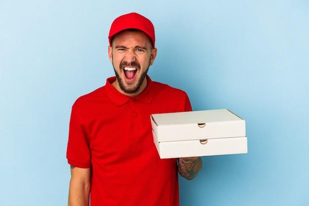 非常に怒って攻撃的な叫び声の青い背景に分離されたピザを保持している入れ墨を持つ若い白人配達人。