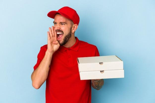 青い背景に分離されたピザを持って叫び、開いた口の近くで手のひらを保持している入れ墨を持つ若い白人配達人。