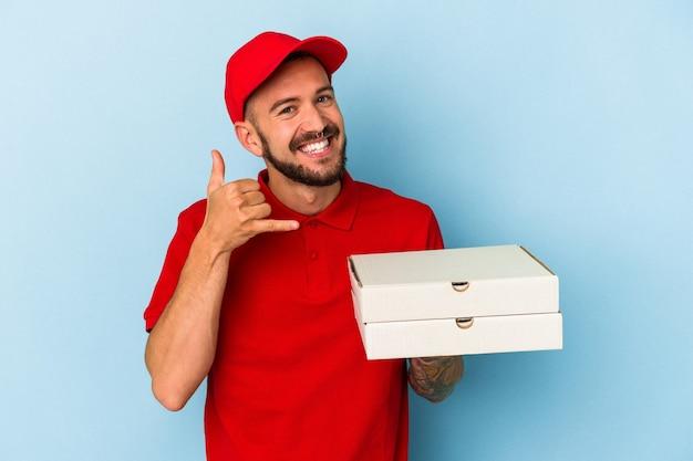 指で携帯電話の呼び出しジェスチャーを示す青い背景で隔離のピザを保持している入れ墨を持つ若い白人配達人。