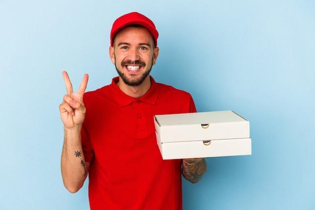 指で2番目を示す青い背景で隔離のピザを保持している入れ墨を持つ若い白人配達人。