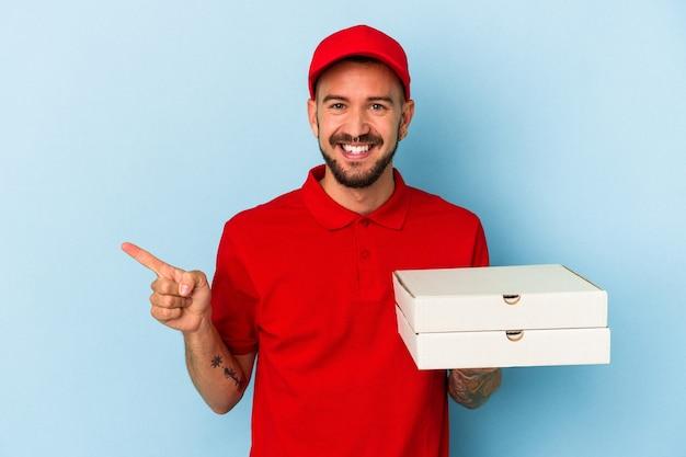 青い背景に分離されたピザを持って笑顔で脇を指して、空白のスペースで何かを示している入れ墨を持つ若い白人配達人。