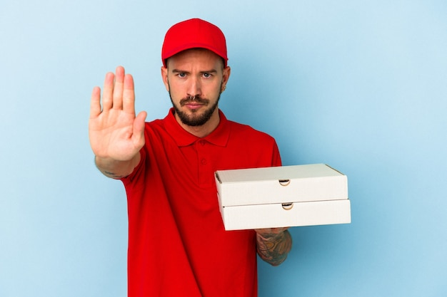 青い背景に分離されたピザを保持している入れ墨を持つ若い白人配達人は、一時停止の標識を示している手を伸ばして立って、あなたを防ぎます。