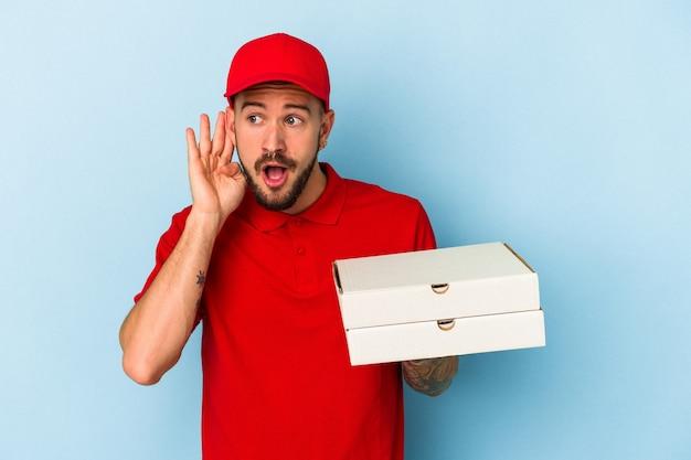ゴシップを聴こうとしている青い背景で隔離のピザを保持している入れ墨を持つ若い白人配達人。