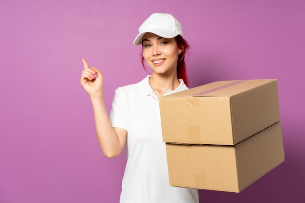 Young caucasian delivery woman holding boxes over purple wall
