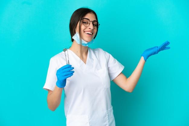 青い背景に分離されたツールを保持している若い白人の歯科医の女性