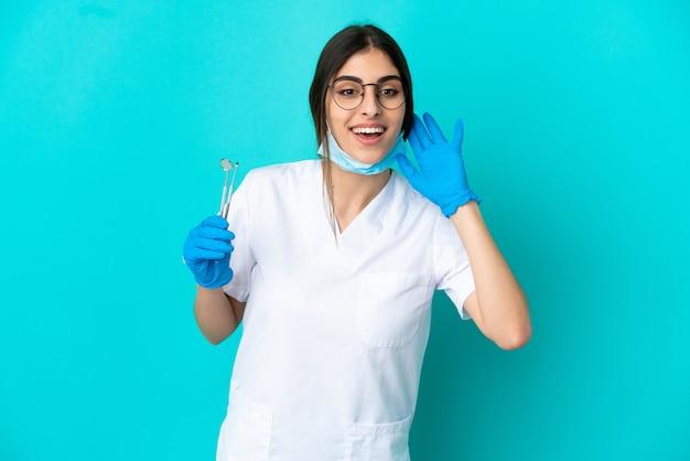 Молодая кавказская женщина-дантист держит инструменты, изолированные на синем фоне, слушая что-то, положив руку на ухо