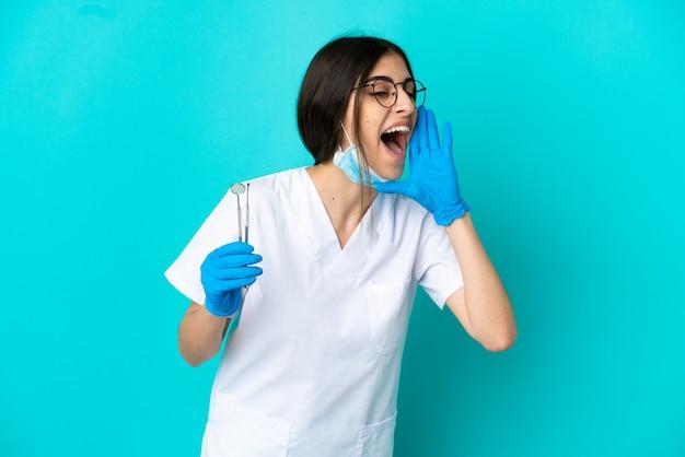 Молодая кавказская женщина-дантист, держащая инструменты, изолированные на синем фоне, кричит с широко открытым ртом в сторону