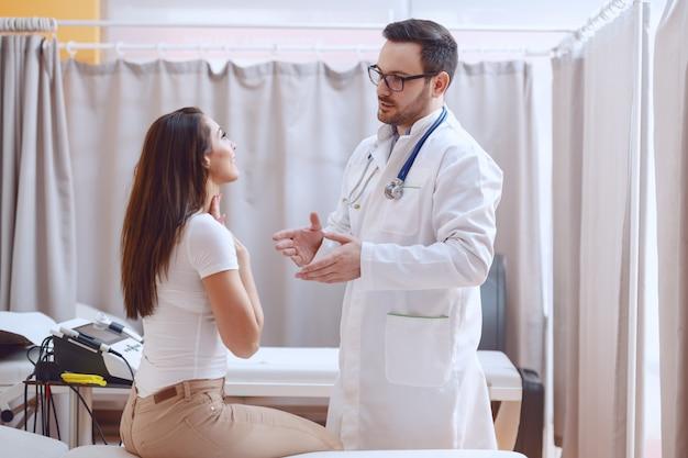 病院に立っている間患者の喉を調べる白い制服を着た若い白人医師。