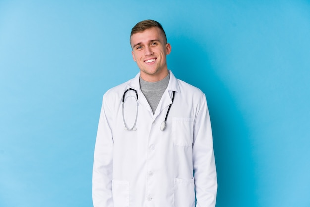 Young caucasian doctor man happy, smiling and cheerful.