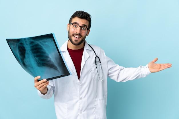 Молодой кавказский доктор человек над изолированной голубой стеной