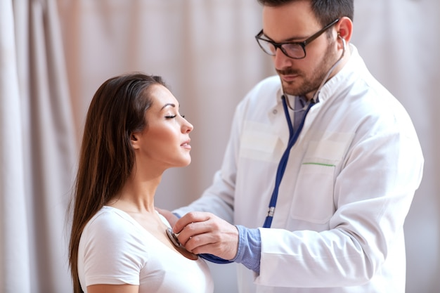 Young caucasian doctor using stethoscope to examine patient's lungs. patient having eyes closed and breathing deeply.