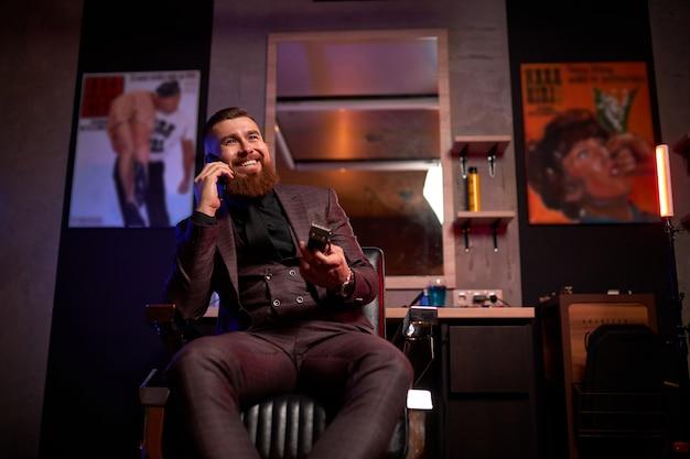 Молодой кавказский элегантный мужчина-парикмахер держит в руках электрическую бритву и разговаривает по телефону