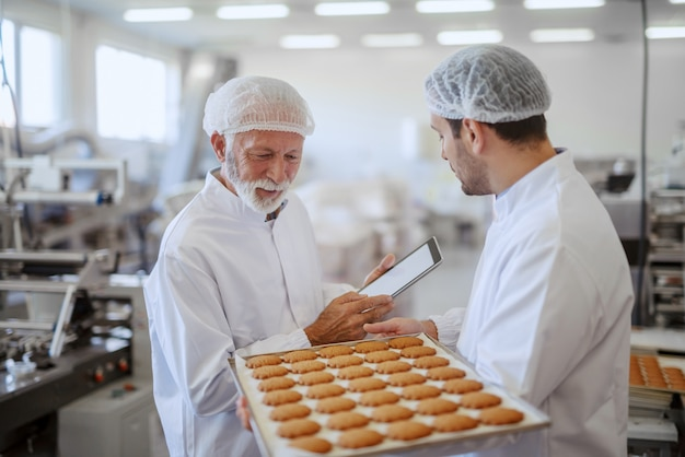 Young caucasian employee holding tray with fresh cookies while supervisor evaluating quality and holding tablet. both are dressed in sterile white uniforms and having hairnets. food plant interior.