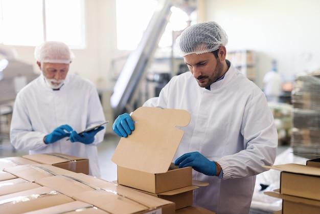 Молодой кавказский сотрудник в стерильной униформе упаковывает товары в ящики. на заднем плане руководитель держит планшет и счетные коробки.