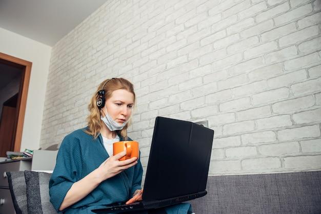 コロナウイルスのパンデミックが原因で自宅でリモートで作業中にソファーでラップトップを使用して、お茶のカップを保持しているヘッドフォンで若い白人ヨーロッパ女性