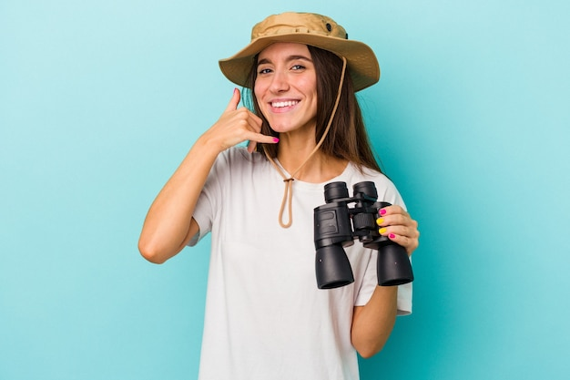 Young caucasian explorer woman holding binoculars isolated on blue background showing a mobile phone call gesture with fingers.