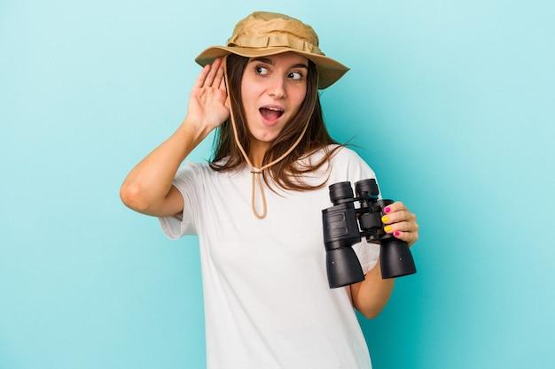 ゴシップを聴こうとしている青い背景に分離された双眼鏡を保持している若い白人探検家の女性。