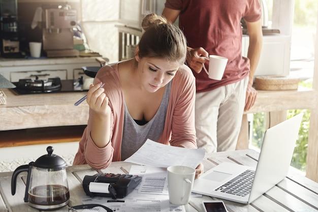 Молодая кавказская семья сталкивается с финансовыми проблемами. обычная женщина, держащая лист бумаги и ручку, заполняет документы при оплате коммунальных услуг, используя калькулятор и универсальный портативный компьютер