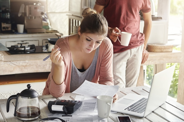 Young caucasian family facing financial problem. casual woman holding piece of paper and pen, filling in documents while making payments for utilities, using calculator and generic laptop computer