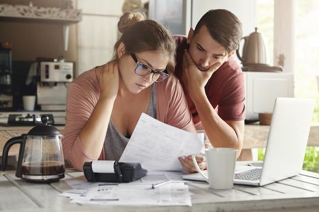 Молодая кавказская семья, имея долговые проблемы, не в состоянии погасить кредит. женщина в очках и брюнетка мужчина изучает бумажную форму банка при управлении внутренним бюджетом вместе в интерьере кухни