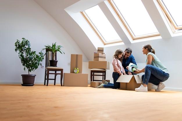 젊은 백인 가족이 새 집으로 이사하고 함께 상자를 풀고 있습니다.