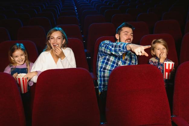 Молодая кавказская семья смотрит фильм в кинотеатре, доме или кинотеатре. выглядите выразительно, удивленно и эмоционально. сидеть в одиночестве и веселиться. отношения, любовь, семья, детство, выходные. Бесплатные Фотографии