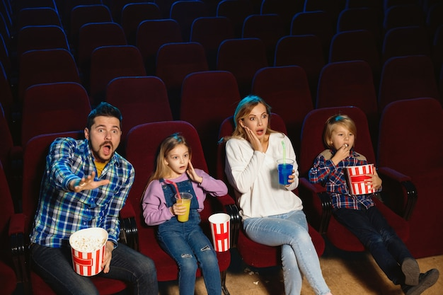Young caucasian family watching a film at a movie theater, house or cinema. look expressive, astonished and emotional. sitting alone and having fun. relation, love, family, childhood, weekend time.