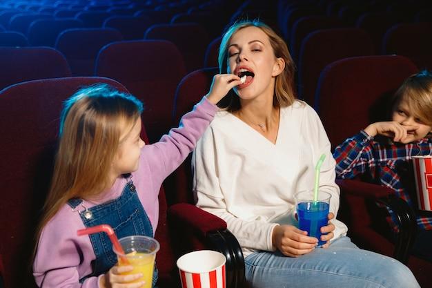 Giovane famiglia caucasica guardando un film in un cinema, casa o cinema. guarda espressivo, stupito ed emotivo. seduto da solo e divertendomi. relazione, amore, famiglia, infanzia, fine settimana.