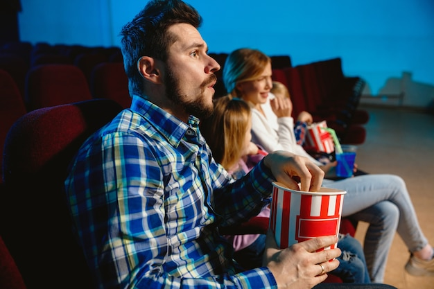 Young caucasian family watching a film at a movie theater, house or cinema.