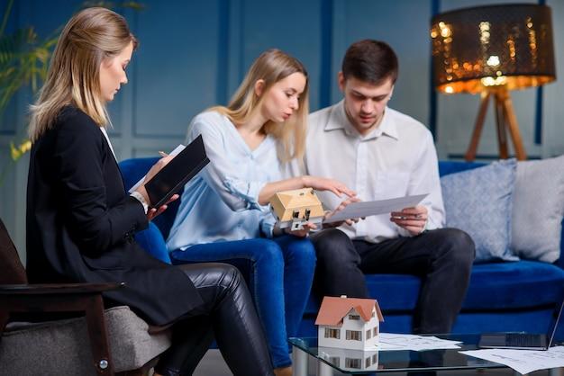 Молодая кавказская семья с дизайнером на встрече в современном голубом офисе.