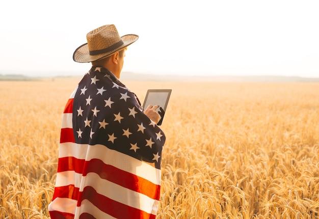 Young caucasian farmer energetically raised the american flag in a  field
