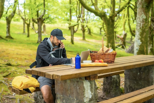 A young caucasian father teleworking sitting at a picnic table with his computer and talking on the phone, with the boy in his backpack