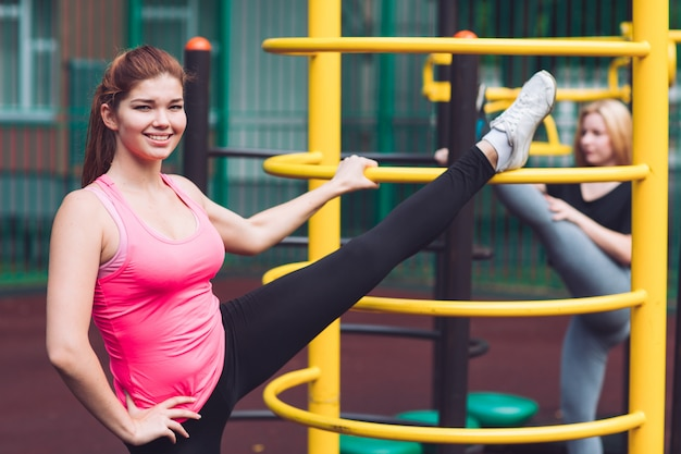A young caucasian female athlete practicing leg rides on the sports gym for active outdoor recreation. summer sports and healthy lifestyle.