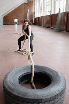 Молодая кавказская спортсменка тянет тяжелую шину боевой веревкой во время тренировки в спортивном зале