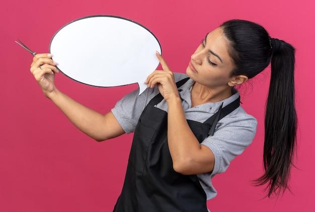 Молодая кавказская женщина-парикмахер в униформе держит речевой пузырь и ножницы, глядя на речевой пузырь, изолированный на розовой стене