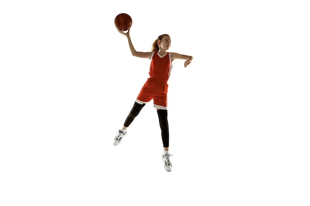 Young caucasian female basketball player in action, motion in jump isolated on white background. redhair sportive girl. concept of sport, movement, energy and dynamic, healthy lifestyle. training.