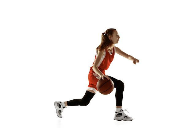 Young caucasian female basketball player in action, motion in run isolated on white background. redhair sportive girl. concept of sport, movement, energy and dynamic, healthy lifestyle. training.