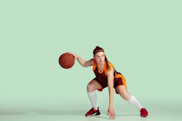 動作中の若い白人女性バスケットボール選手、ミント色の背景に分離されたゲームプレイ中の動き。スポーツ、運動、エネルギー、ダイナミックで健康的なライフスタイルのコンセプト。トレーニング、練習。